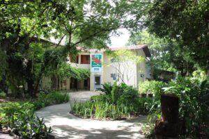 Fotografia de uma casa rodeada de muitas árvores e plantas, é a sede do Herbário MAC, em Alagoas.