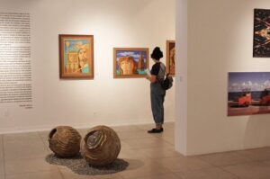 Fotografia de uma das salas de exposição da Pinacoteca da Universidade Federal de Alagoas, temos uma jovem mulher observando quadros enquanto segura um caderno, próximo a ela temos duas esculturas no chão da sala, em fomato circular