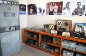 Imagem de uma sala com diversos equipamentos antigos de rádio e várias fotografias na parede.