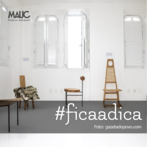 """Fotografia de divulgação do Museu das Cadeiras Brasileiras, na parte inferior da imagem temos um faixa preta com os dizeres """"#ficaadica"""" e """"foto: gazetadopovo.com"""", na parte superior esquerda da imagem se encontra a logo do MAUC, ao fundo uma parede branca com três janelas também brancas, na frete da parede temos três cadeiras de diferentes tamanhos na cor marrom."""