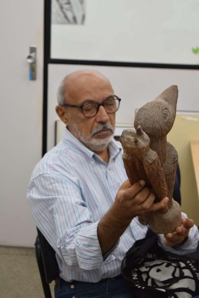 Foto do professor Gilmar de Carvalho segurando uma escultura de madeira, no Mauc.